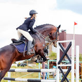 Sportswoman jumping over obstacles on competition Stock Images
