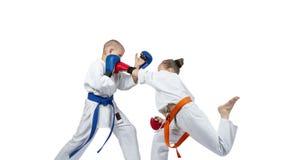 Sportswoman in karategi beats gyaku-tsuki in the jump Stock Image