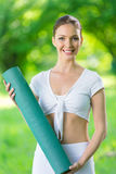 Sportswoman keeping mat Stock Image