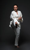 Sportswoman kicks forward right leg Royalty Free Stock Photos
