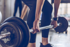 Sportswoman lifting barbell at gym workout. Close-up partial view of sportswoman lifting barbell at gym workout Royalty Free Stock Images
