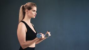 Sportswoman lifting iron dumbbells during biceps muscles workout isolated. Medium shot on RED camera