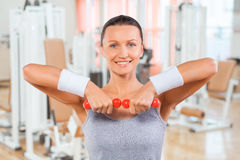 Sportswoman lifting weights with two small dumbbell Royalty Free Stock Photo