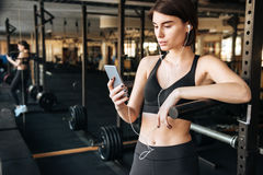 Sportswoman listening to music with cell phone in gym. Beautiful young sportswoman listening to music with cell phone in gym Stock Photos