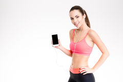 Sportswoman listening to music from smartphone with blank screen Royalty Free Stock Photo
