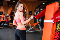 Sportswoman listening to music and training in gym Stock Photography