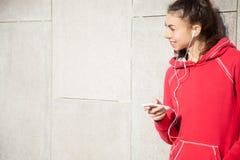 Sportswoman listening to music using phone app Stock Image