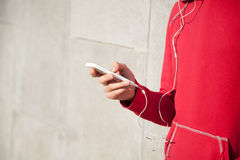 Sportswoman listening to music using smartphone Royalty Free Stock Photography