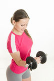 Sportswoman looking at dumbbell in the right hand Stock Photo