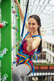 Sportswoman is making a thumb up gesture while climbing on the w Stock Images