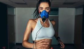Sportswoman with mask running on treadmill in gym Royalty Free Stock Images