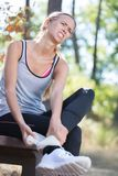Sportswoman massaging injured ankle after sport accident Royalty Free Stock Image