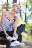 Sportswoman massaging injured ankle after sport accident Lizenzfreies Stockbild