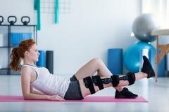 Sportswoman on mat doing exercises with broken leg stock image