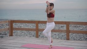 Sportswoman is meditating in garudasana, eagle pose in seacoast. Yoga master woman is performing eagle pose, crossing legs and hands. She is training and stock footage