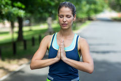 Sportswoman meditating with hands joined Stock Photography