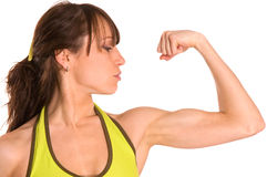 Sportswoman muscles. Sportswoman look at her muscles Royalty Free Stock Photos