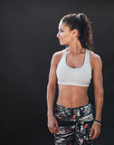 Sportswoman with muscular body on black background Stock Photos