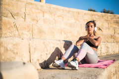 Sportswoman outdoor in a stairs doing exercise listening music. Sports woman outdoor in a stairs doing exercise listening music royalty free stock images