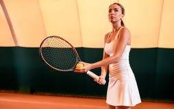 Sportswoman på tennisbanan med racqueten Arkivbild