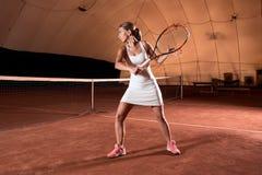 Sportswoman på tennisbanan med racqueten Arkivbilder