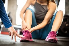 Pain in leg. Sportswoman with personal trainer in gym. Sports women having injury leg. Close up. Focus is on legs stock photos