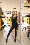 A sportswoman poses standing, holding a metal barbell in the gym. A beautiful European sportswoman, a blonde with long hair, is dressed in a black tight-fitting Stock Photos