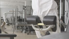 Sportswoman in protective suit and respirator training back muscles on equipment in gym. Portrait of Caucasian woman