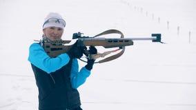 Sportswoman is ready to shoot during biathlon race. 4K stock footage
