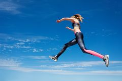 Sportswoman remains in air while jumping Stock Photo