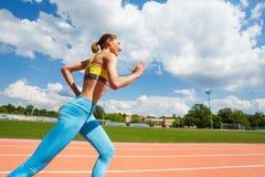 Sportswoman running outdoor at stadium`s racetrack Royalty Free Stock Photos