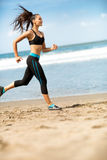 Sportswoman running outdoors on blue sea Stock Photography