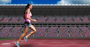 Sportswoman running on tracks against buildings. Digital composite of Sportswoman running on tracks against buildings Royalty Free Stock Image