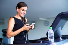 Sportswoman running on treadmill and listening to music In fitness center. stock photo