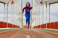 Sportswoman runs on the bridge, legs in sneakers close-up. royalty free stock photography