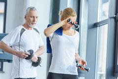 Sportswoman and senior sportsman training with dumbbells Royalty Free Stock Photography