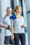 Sportswoman and senior sportsman training with dumbbells. In sports center Stock Photos