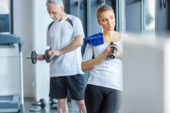 Sportswoman and senior sportsman training with dumbbells. In sports center Stock Image