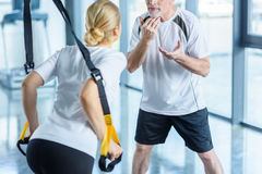 Sportswoman and senior trainer training with resistance band Royalty Free Stock Image