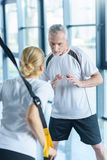 Sportswoman and senior trainer training with resistance band Stock Images