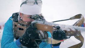 Sportswoman is shooting from her riffle during a biathlon race in a lying position. HD stock footage