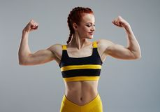 Sportswoman showing biceps with both hands. In studio Stock Image