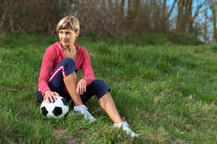 Sportswoman Sitting with a Ball Stock Image