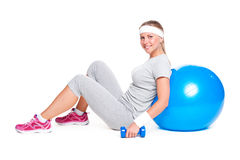 Sportswoman sitting with ball and dumbbells Royalty Free Stock Images
