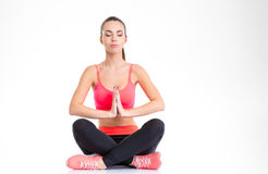 Sportswoman sitting with crossed legs, folded palms and closed eyes Stock Photos