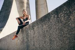 Sportswoman resting after physical training session. Sportswoman sitting outdoors after physical training session outdoors. Female athlete taking a break after Royalty Free Stock Photo