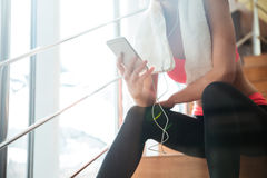 Sportswoman sitting and using smartphone with earphones in gym. Closeup of sportswoman with white towel sitting and using smartphone with earphones in gym Stock Images