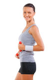 Sportswoman smiling holding small dumbbells isolated on white ba Stock Photos