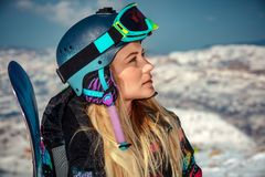 Sportswoman with snowboard. Portrait of a sportswoman wearing helmet and mask with snowboard in hand looking a side, enjoying sunny frosty day, perfect day for stock image