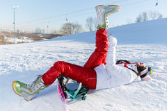 Sportswoman with snowboard in sportswear. Lies on snow in ski resort Royalty Free Stock Image